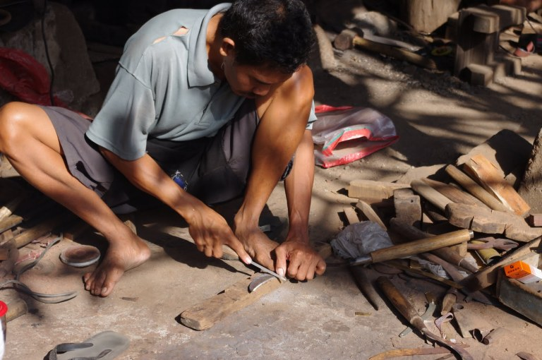 Erik from Around this World has submitted  a picture from Bali, Indonesia. The blacksmith is putting his hands (and feet) to work while sharpening the blade on a sickle. Balinese people have been producing metal items swords, instruments, and other items using this same method for thousands of years.